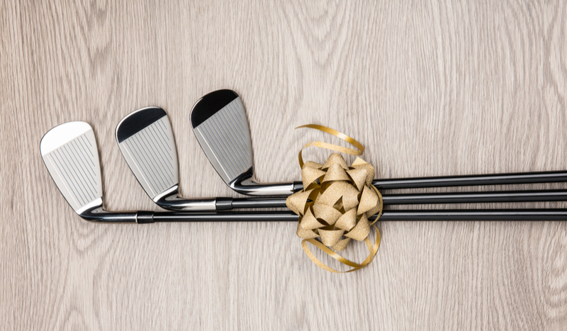 Three fundraising golf clubs tied with a golden bowtie laying on hardwood floor.